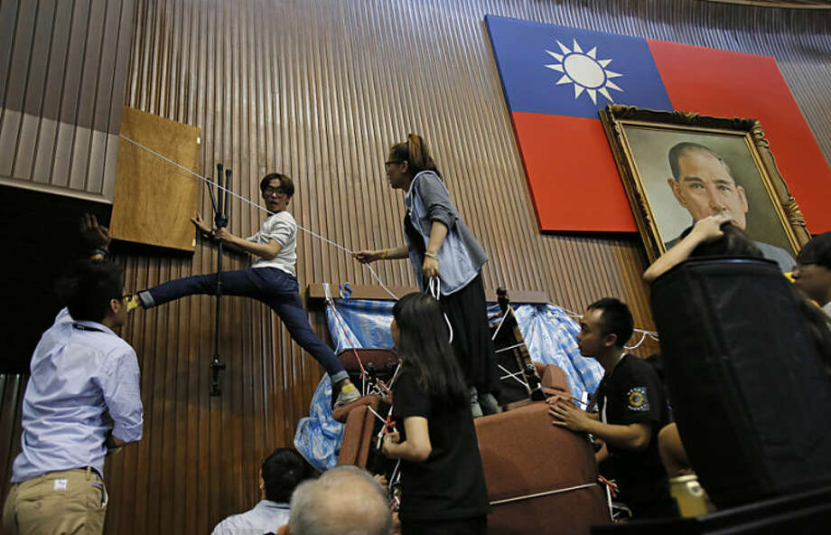Student protesters against a trade pact with China remove barricades before peacefully leaving the legislature in Taipei, Taiwan, Thursday, April 10, 2014. The students who have occupied Taiwan's Parliament for 24 days left Thursday evening after receiving assurances the deal they see as imperiling the island's autonomy would undergo legislative review. (AP Photo/Wally Santana)