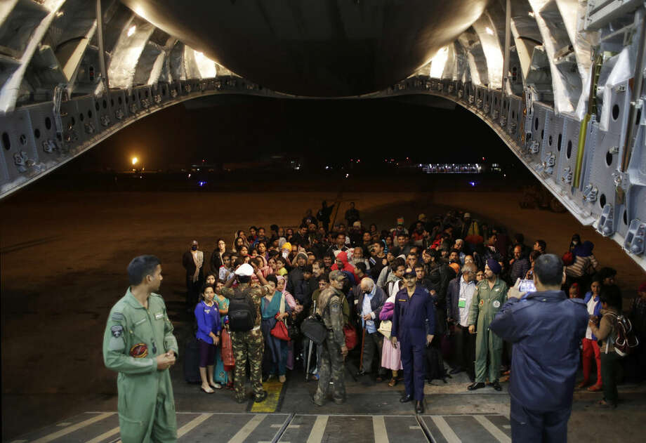 Survivors of Saturday's earthquake wait to board a military plane evacuating injured and stranded Indians from Kathmandu to New Delhi during a midnight rescue mission by Indian Air Force, in Kathmandu, Nepal, Wednesday, April 29, 2015. (AP Photo/Altaf Qadri)