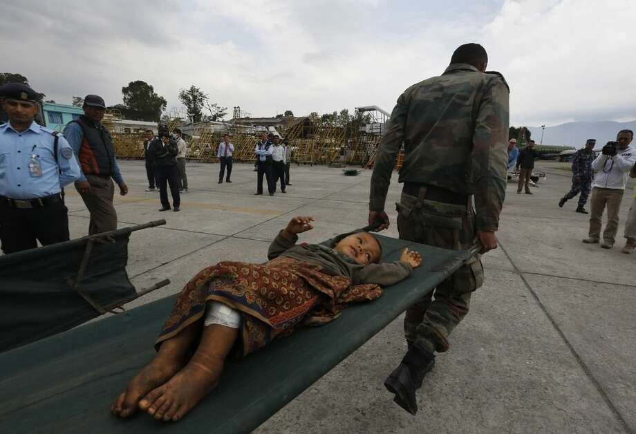 A Nepalese child injured in Saturday's earthquake is taken on a stretcher after being evacuated from higher reaches of mountains by Nepalese army soldiers, in Kathmandu, Nepal, Wednesday, April 29, 2015. The first aid shipments reached a hilly district near the epicenter of Nepal's earthquake, a U.N. food agency official said, and distribution of food and medicine would start Wednesday, five days after the quake struck. (AP Photo/Manish Swarup)