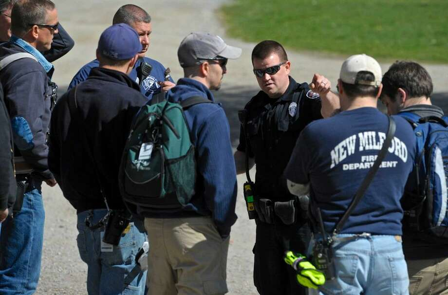 New Milford Police Officer Brian Peloso, center, gives descriptions and names of missing hikers as part of a search and rescue drill in Clatter Valley Park on Saturday, April 16, 2016, in New Milford, Conn. Officer Peloso was first responder on scene for the drill.
