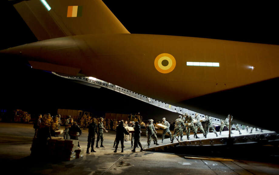 Nepalese army personnel unload supplies from a military plane evacuating injured and stranded Indians from Kathmandu to New Delhi during a midnight relief and rescue mission by Indian Air Force, in Kathmandu, Nepal, Wednesday, April 29, 2015. (AP Photo/Altaf Qadri)