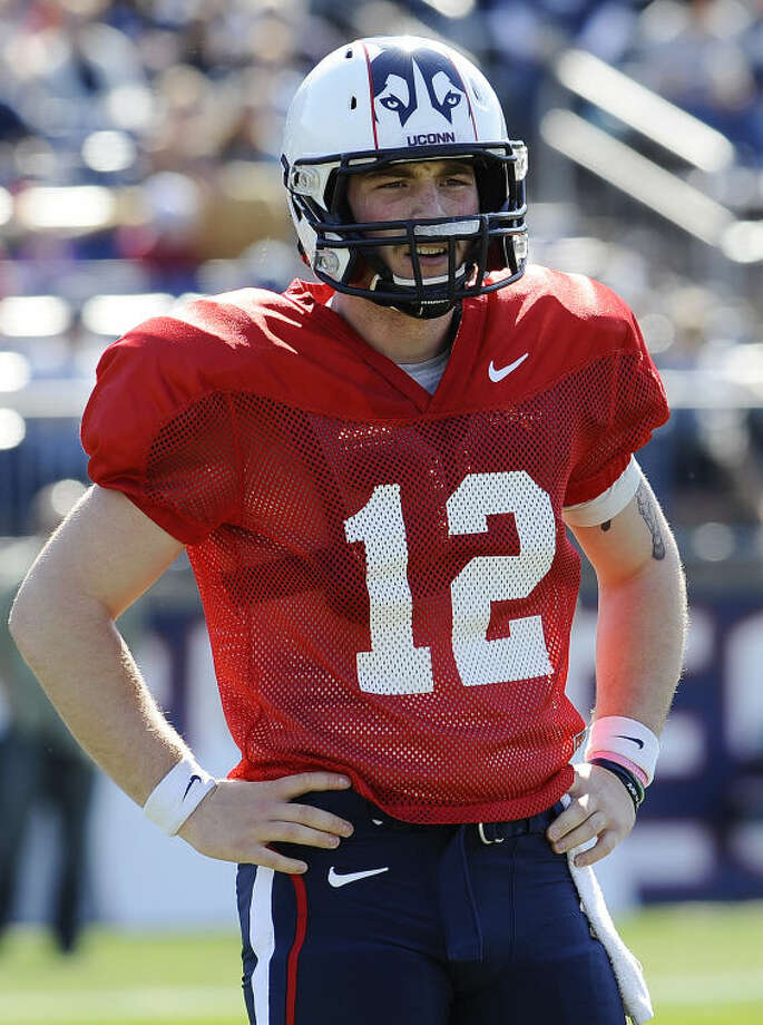 Connecticut quarterback Casey Cochran listens to instructions from a coach during the first half of UConn's Blue-White spring NCAA college football game at Rentschler Field, Saturday, April 12, 2014, in East Hartford, Conn. (AP Photo/Jessica Hill)