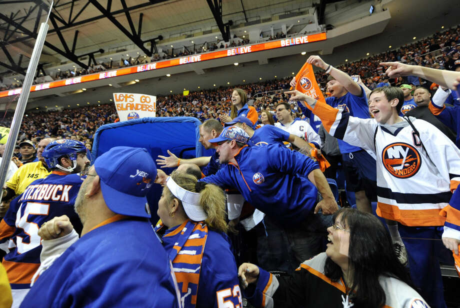 New York Islanders fans cheer New York Islanders right wing Cal Clutterbuck (15) and teammates as they leave the ice after beating the Washington Capitals 3-1 in Game 6 of a first-round NHL Stanley Cup hockey playoffs at Nassau Coliseum on Saturday, April 25, 2015, in Uniondale, N.Y. (AP Photo/Kathy Kmonicek)