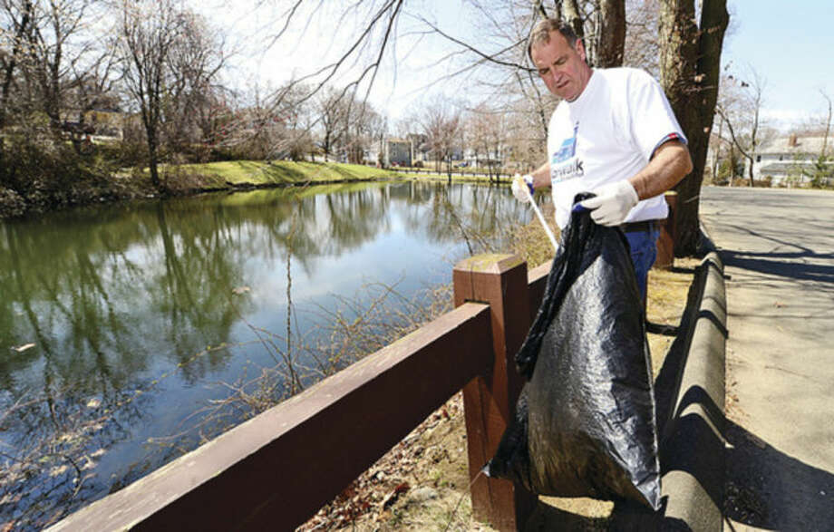 Hour photo / Erik Trautmann Keep Norwalk Beautiful's David Shockley assists students from Fairfield University as they help clean up Flax Hill Park as part of the Keep Norwalk Beatiful intiative Saturday.