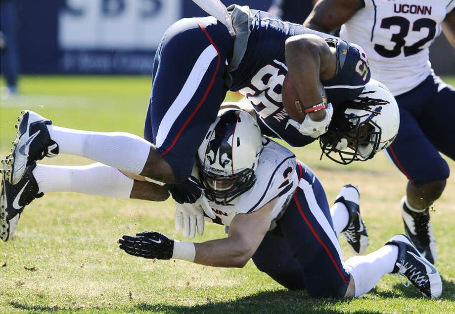 Connecticut blue teams's Geremy Davis, top, is tackled by white's Graham Stewart during the first half of UConn's Blue-White spring NCAA college football game at Rentschler Field, Saturday, April 12, 2014, in East Hartford, Conn. (AP Photo/Jessica Hill)