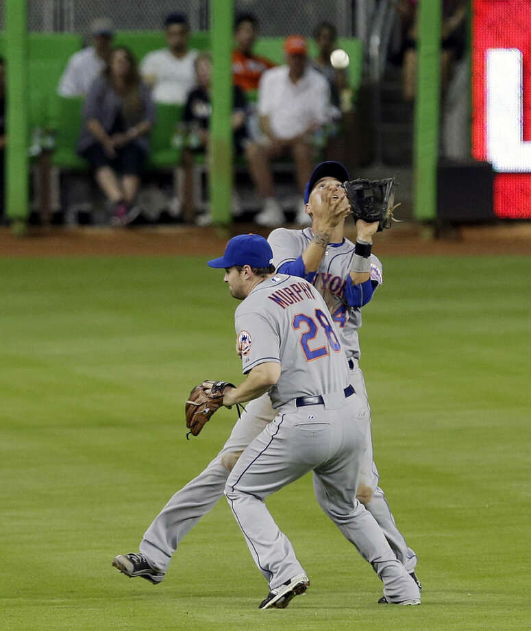 New York Mets shortstop Wilmer Flores (4) prepares to catch a pop-up in shallow left field by Miami Marlins' Adeiny Hechavarria (3) as second baseman Daniel Murphy (28) avoids a collision in the fourth inning of a baseball game, Wednesday, April 29, 2015, in Miami. (AP Photo/Alan Diaz)