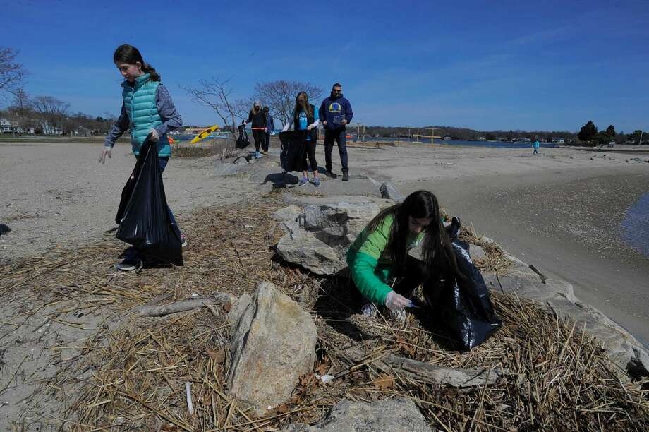 Madison Hart, left and Caroline Steib, at right, both sixth-graders at King Academy, collect garbage along the main beach at Cove Island Park in Stamford on April 16, 2016. They were part of a group of families from the school in Stamford participating in King Cares Day, where students volunteer to complete two hours of community service. The group of 20 collected over 300 pounds of trash, that included plastics, discarded diapers, fishing lines and broken pieces of Styrofoam.