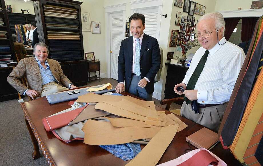 Umbeto Pitagora and clients Thomas Vozzella and Gene Venanzi share a laugh looking over the pattern for Vozzella's suit, which Umberto custom tailors with one arm longer by an inch because of years of playing golf.