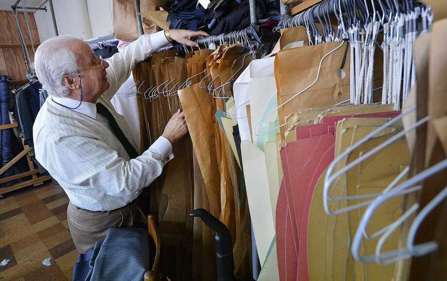 Umberto Pitagora finds a suit pattern for a customer at Umberto the Tailor in Wilton Center.