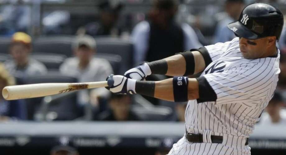 New York Yankees' Carlos Beltran follows through on a two-run home run during the first inning of a baseball game against the Boston Red Sox Saturday, April 12, 2014, in New York. (AP Photo/Frank Franklin II)
