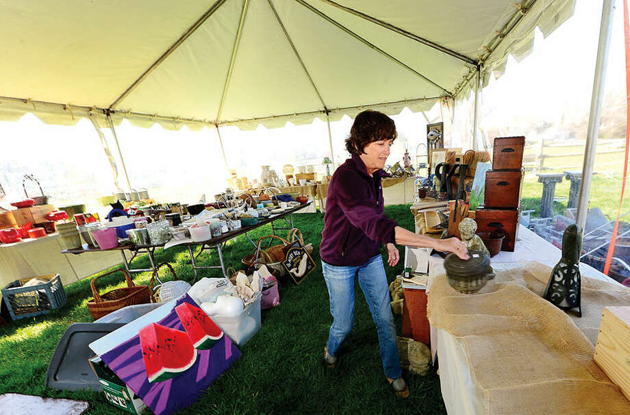 Hour photo / Erik Trautmann Rowayton Gardeners member Frani Taylor sets up the Tage Sale tent for their annual Spring Plant Sale this Saturday.