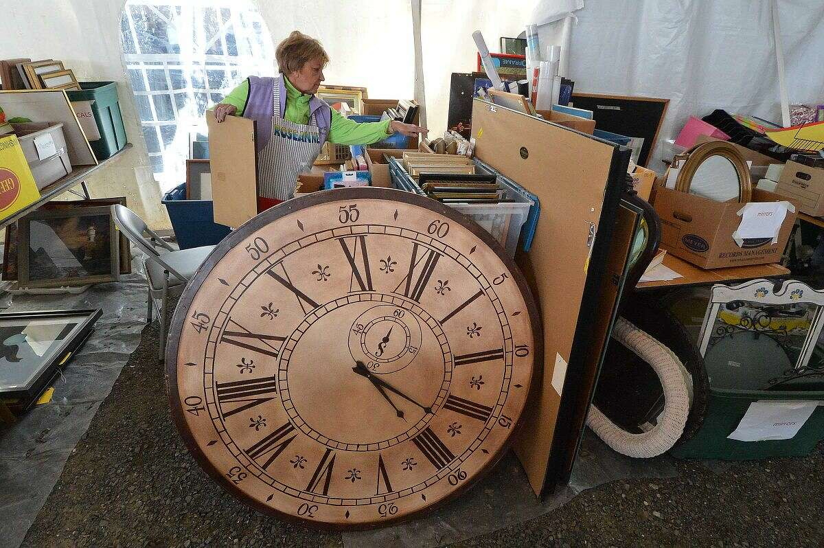 Volunteer Roseanne Forslund works in the new tent that holds frames, artwork, books, and just about anything you may need, including a giant artistic clock at Minks to Sinks.