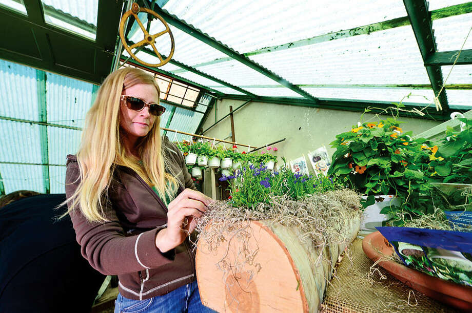 Hour photo / Erik Trautmann Rowayton Gardeners member Tory Woodruff makes potted plant designs for their annual Spring Plant Sale this Saturday.