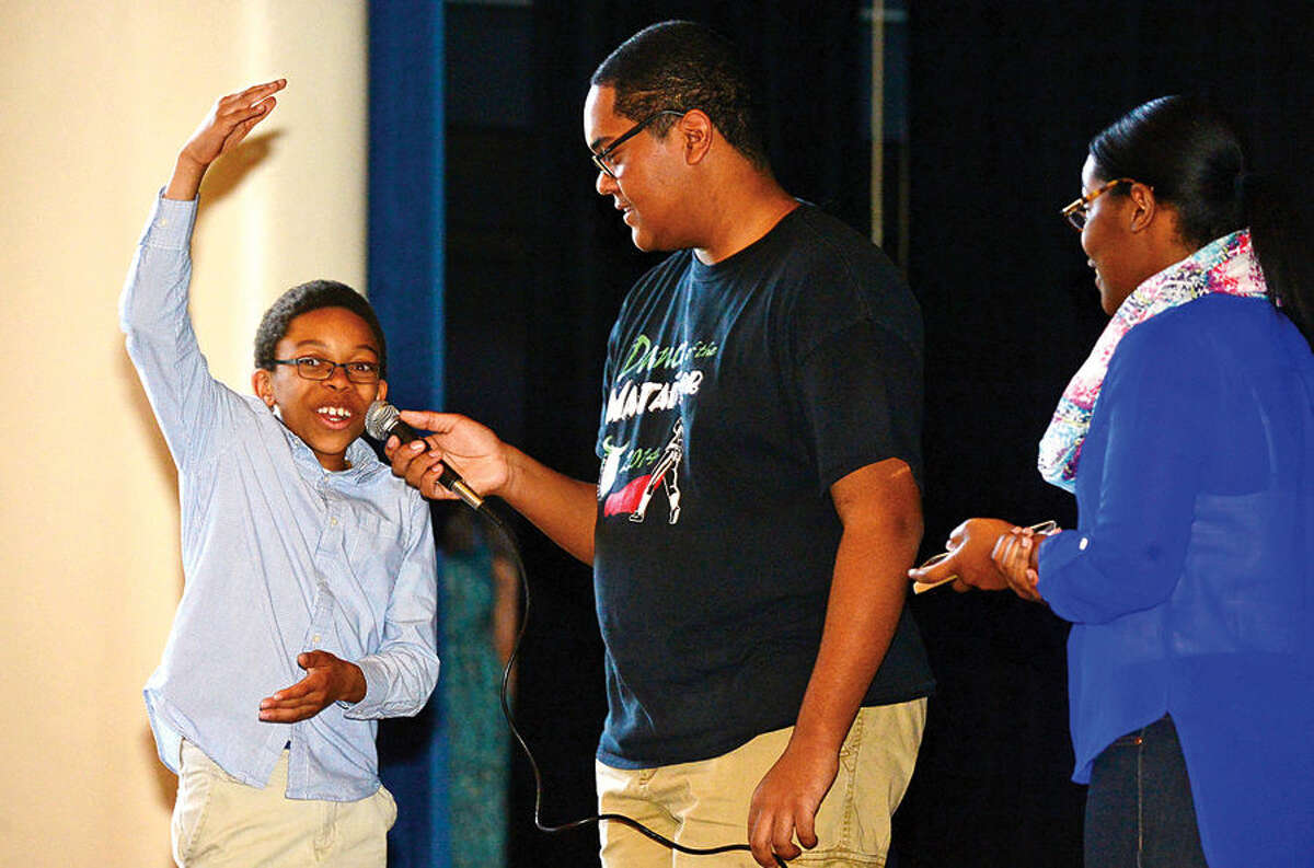 Hour photo / Erik Trautmann Nathan Hale Middle School 6th grader Allen Counts answers a question on bullying from Norwalk High School Peace Works program members Daniel Smith and Seliana Seradieau as they make a anti-bullying presentation to students at the middle school Thursday.