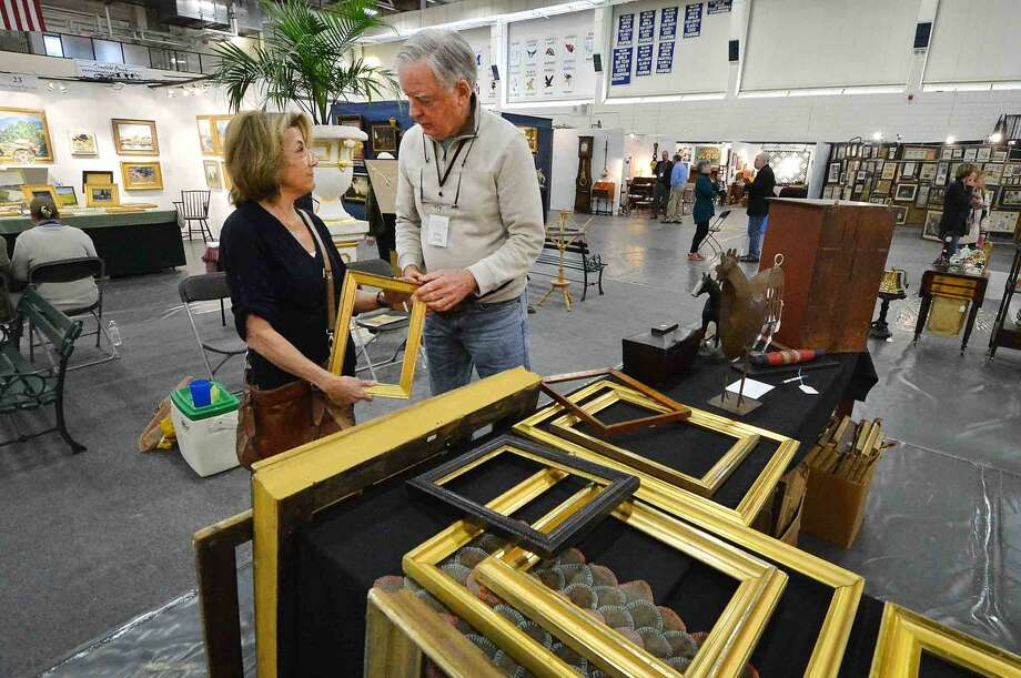 John Gould with Joseph Collins Antiques shows artist Melinda Fager some vintage frames at The Wilton Spring Antiques Show at Wilton High School Field House on Sunday April 17, 2016