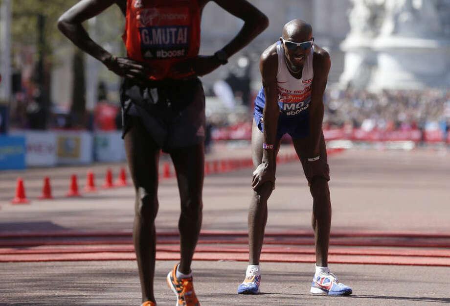Mo Farah of Britain, running his first London marathon, looks on as he crosses the finish line in eighth place during the London Marathon in London, Sunday, April 13, 2014. (AP Photo/Sang Tan)