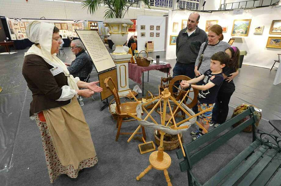 Wilton Historical Society volunteer Moira Craw demonstrates weaving at The Wilton Spring Antiques Show at Wilton High School Field House on Sunday April 17, 2016