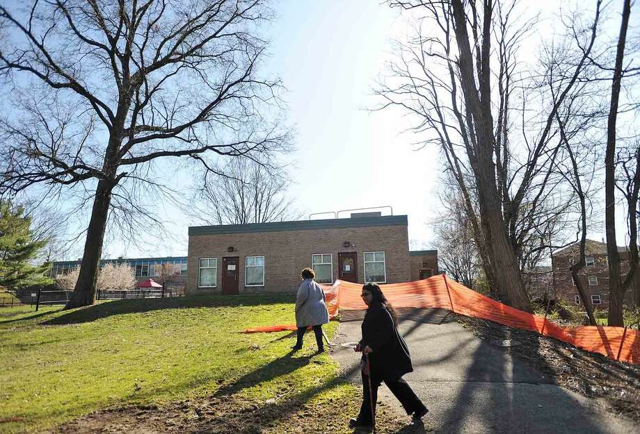 Community advocate and fellow Roodner Court resident Deidra Davis, left, and Norwalk Board of Education member Shirley Mosby walk behind the former Nathaniel Ely School in Norwalk, Conn. on Wednesday, April 13, 2016. There is a proposal to open three new schools in the city to deal with overcrowding, including Nathaniel Ely which is adjacent to the Roodner Court public housing complex.