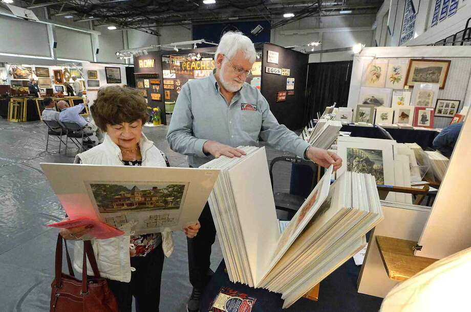 Elanor Gonzalez and Alan Meeds flip through some architectual prints at the Lynne T. Ward Antiques Prints booth during The Wilton Spring Antiques Show at Wilton High School Field House on Sunday April 17, 2016
