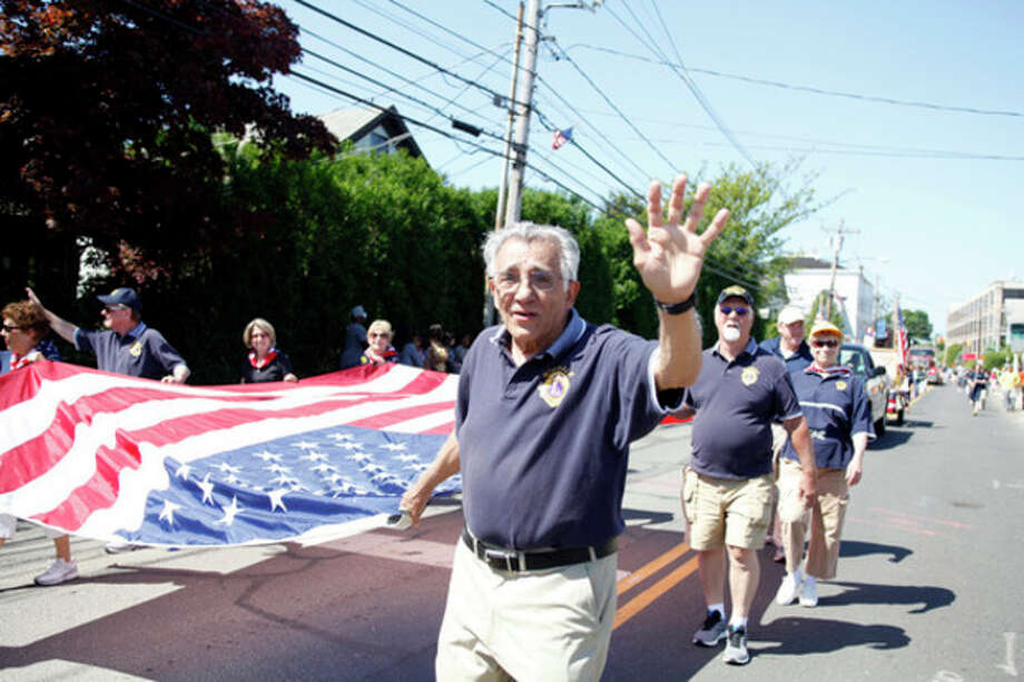 Ed Farris from the Lions Club waves to the crowd as he helps carry a flag during Norwalk's annual Memorial Day Parade Monday morning.Hour Photo / Danielle Robinson