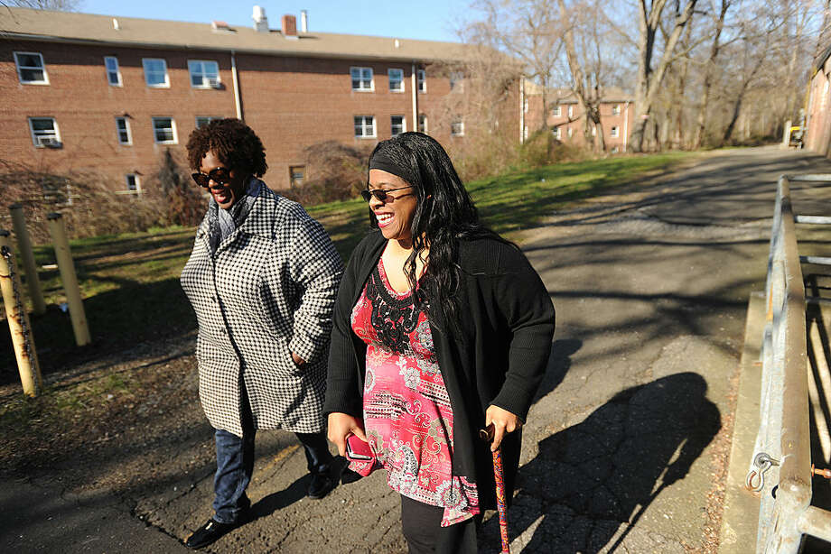 Community advocate and Roodner Court resident Deidra Davis, left, and Norwalk Board of Education member Shirley Mosby walk from the Roodner Court public housing complex to the adjacent former Nathaniel Ely School in Norwalk, Conn. on Wednesday, April 13, 2016. There is a proposal to open three new schools in the city to deal with overcrowding, including the Nathaniel Ely School.