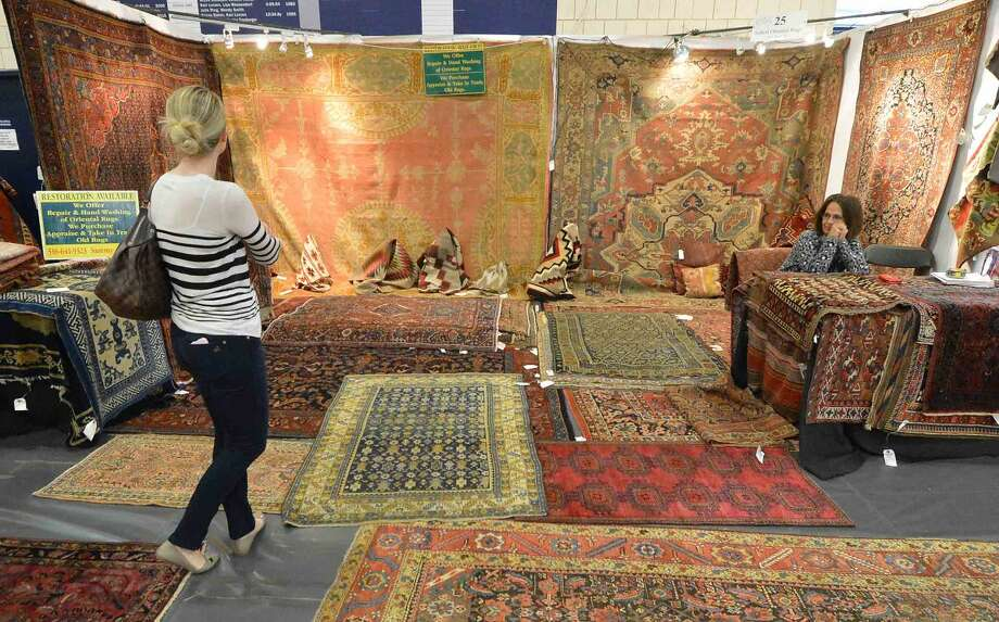 Vintage rugs cover the walls and the floors at the Soheil Oriental Rugs booth at The Wilton Spring Antiques Show at Wilton Hight School on Sunday April 17, 2016