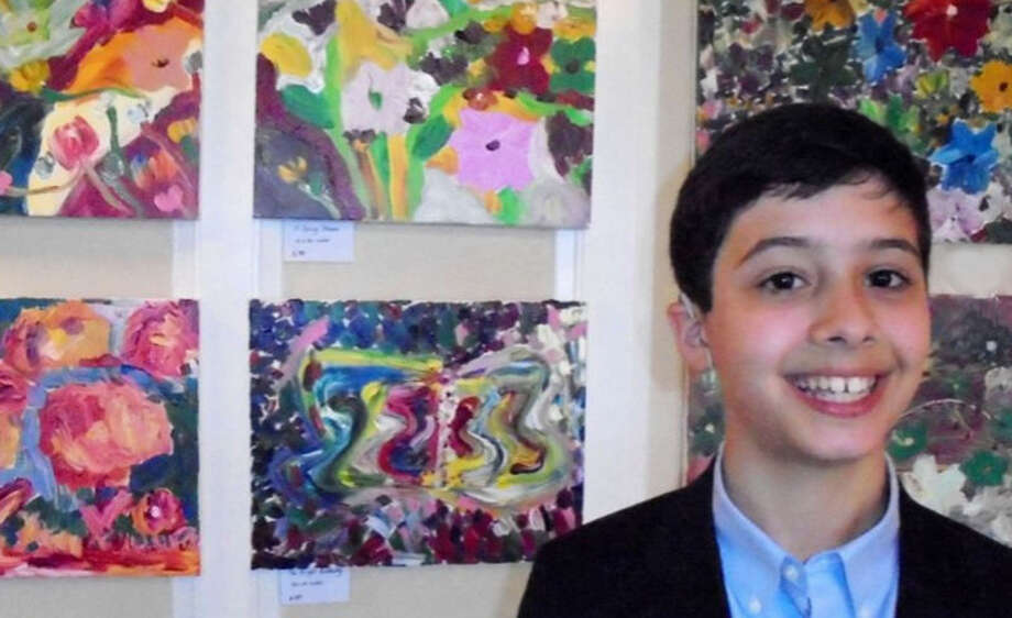 Meg Barone / Hearst Connecticut Media Alex Mussomeli, 11, of Westport, in front of his acrylic paintings during his first solo art show at the Fairfield County Hunt Club, which was a fundraiser for the Hearing Health Foundation.