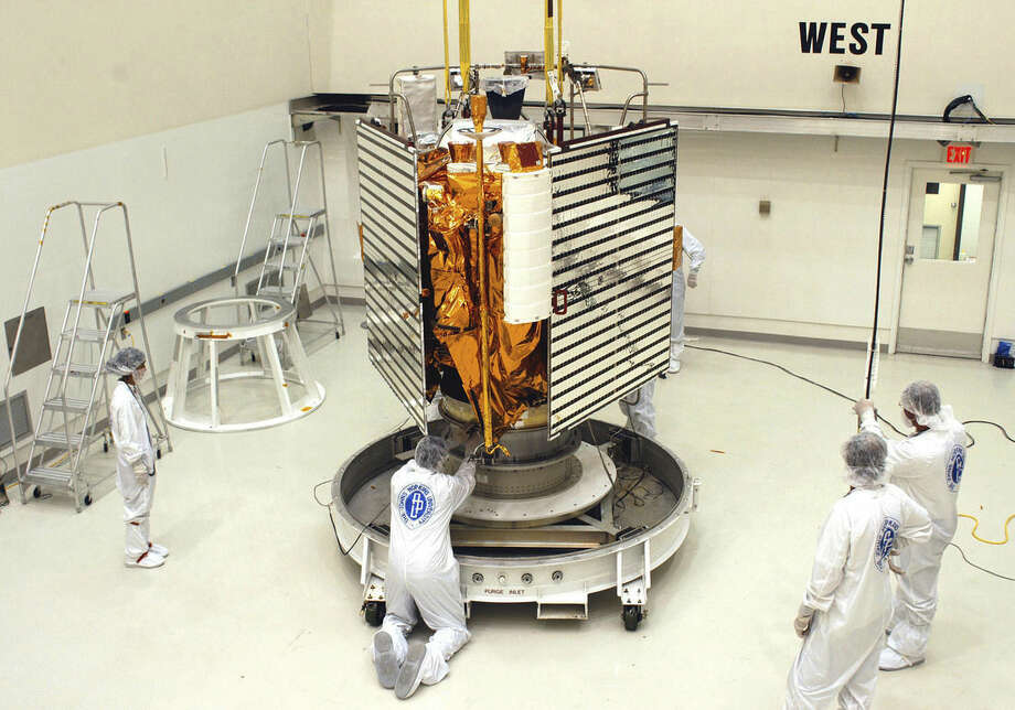 In this undated photo provided by NASA, technicians with The Johns Hopkins University Applied Physics Laboratory in Titusville, Fla., prepare the MESSESNGER spacecraft for a move to a hazardous processing facility in preparation for loading the spacecraft's hypergolic propellants. (NASA via AP)