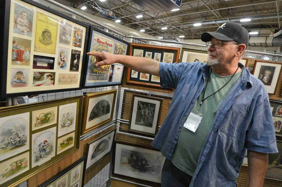 Don Lutz, owner of Chimney Corner Antiques shows some of the framed original advertising art he has framed at The Wilton Spring Antiques Show at Wilton High School Field House on Sunday April 17, 2016