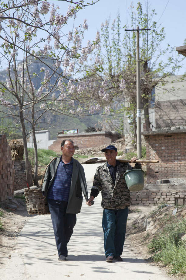 In this April 23, 2015 photo, friends Jia Wenqi, left, and Jia Haixia walk along a lane in Yeli village near Shijiazhuang city in northern China's Hebei province. For the past 13 years, Jia Wenqi, who has no arms, and Jia Haixia, who is blind, have worked together to plant and water more than 12,000 trees near their village. (AP Photo/Helene Franchineau)