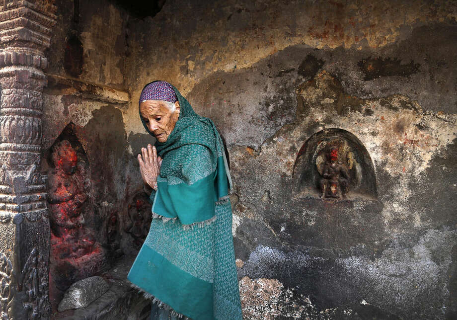An elderly Nepalese woman prays at a temple damaged in an earthquake in Kathmandu, Nepal, Friday, May 1, 2015. The strong magnitude earthquake shook Nepal on Saturday devastating the region and leaving some thousands shell-shocked and displaced. (AP Photo/Manish Swarup)