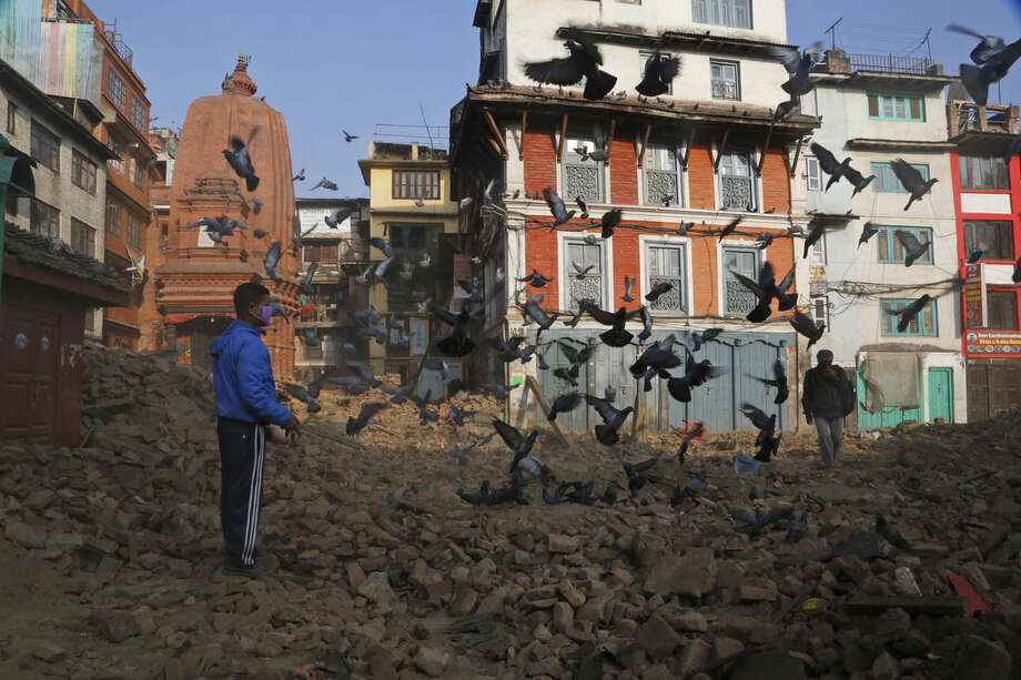 A Nepalese man feeds pigeons as other walkd across the rubble in Kathmandu, Nepal, Friday, May 1, 2015. A strong magnitude earthquake shook Nepal on Saturday devastating the region and leaving some thousands shell-shocked and displaced. (AP Photo/Manish Swarup)