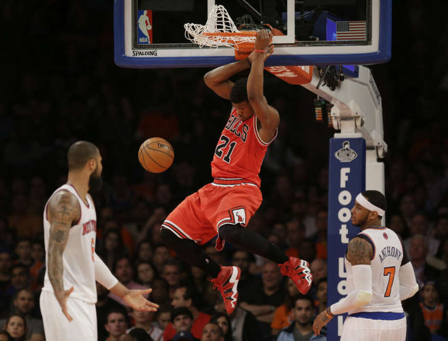 Chicago Bulls' Jimmy Butler dunks the ball while New York Knicks' Tyson Chandler, left, and Carmelo Anthony look on during the first half of the NBA basketball game, Sunday, April 13, 2014 in New York. (AP Photo/Seth Wenig)