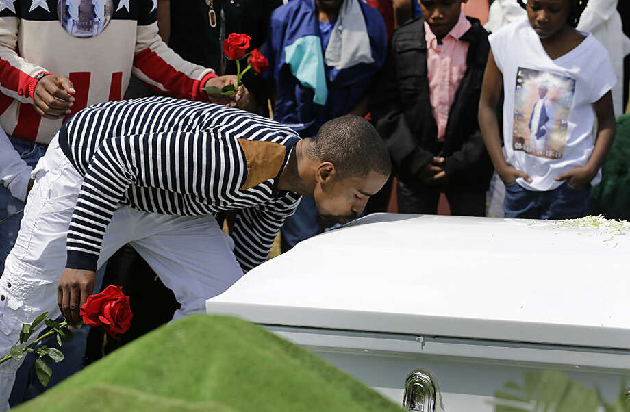 A mourner kisses Freddie Gray's casket before placing a rose on it at Gray's burial, Monday, April 27, 2015, at Woodlawn Cemetery in Baltimore. Gray died from spinal injuries about a week after he was arrested and transported in a Baltimore Police Department van. (AP Photo/Patrick Semansky)