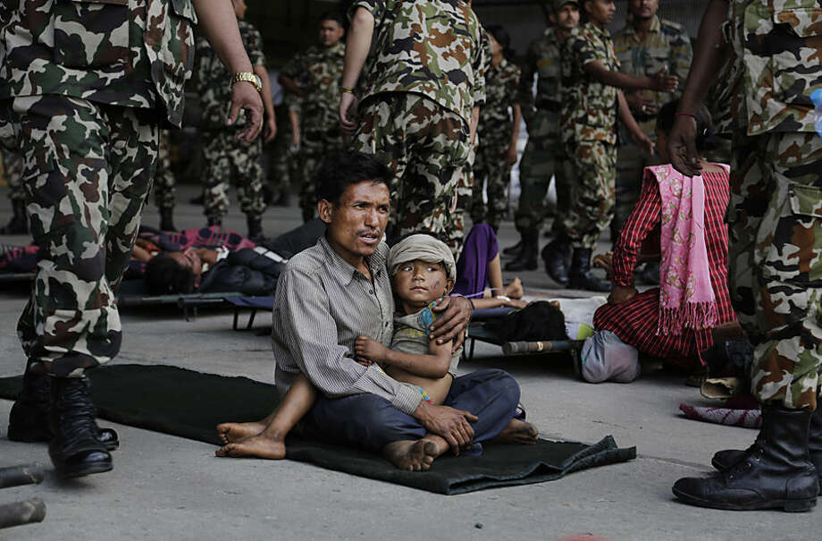 A man sits with a child on his lap as victims of Saturday's earthquake, wait for ambulances after being evacuated at the airport in Kathmandu, Nepal, Monday, April 27, 2015. The death toll from Nepal's earthquake is expected to rise depended largely on the condition of vulnerable mountain villages that rescue workers were still struggling to reach two days after the disaster. (AP Photo/Altaf Qadri)