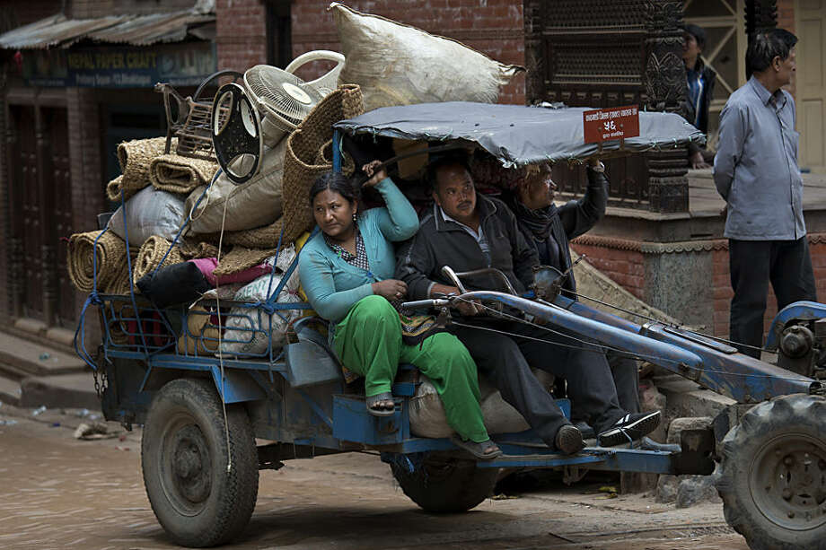 Residents carry their belongings that were retrieved from ruins of their homes after Saturday's earthquake in Bhaktapur, Nepal, Tuesday, April 28, 2015. Many people have camped outdoors in the chilly night cold since Saturday's massive earthquake that shook Nepal's capital and the densely populated Kathmandu valley. (AP Photo/Bernat Armangue)