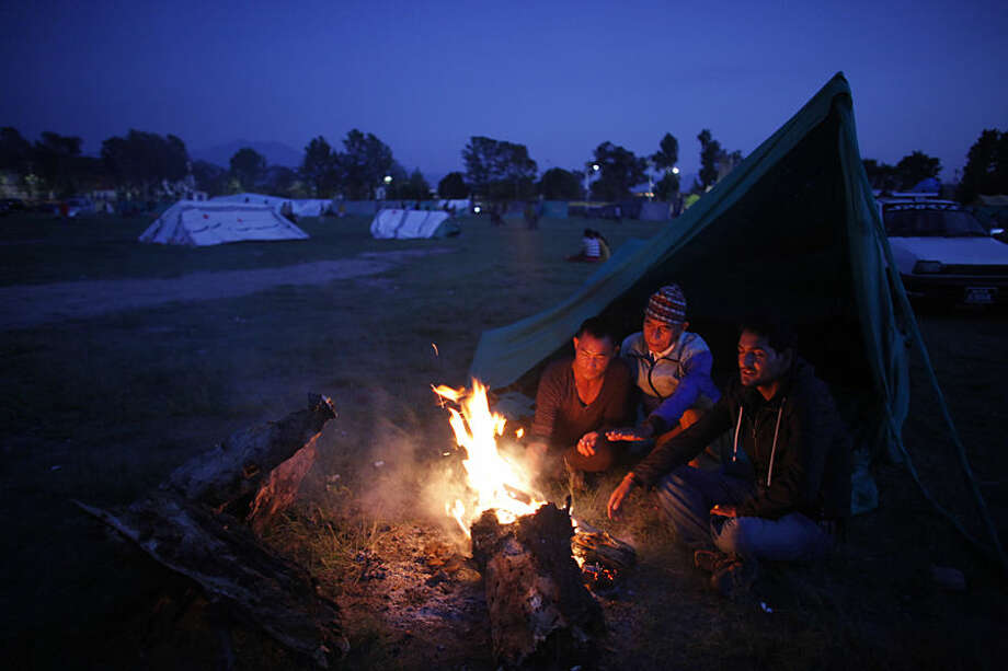 Nepalese people make themselves warm while they stay on open ground from fears of earthquake tremors in Kathmandu, Nepal, Monday, April 27, 2015. A strong magnitude earthquake shook Nepal's capital and the densely populated Kathmandu valley on Saturday devastating the region and leaving tens of thousands shell-shocked and sleeping in streets. (AP Photo/Niranjan Shrestha)