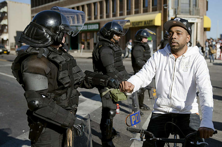 A man on a bicycle greets Maryland State Troopers Tuesday, April 28, 2015, in the aftermath of rioting following Monday's funeral for Freddie Gray, who died in police custody. The violence that started in West Baltimore on Monday afternoon had spread to East Baltimore and neighborhoods close to downtown and near Camden Yards. (AP Photo/Matt Rourke)
