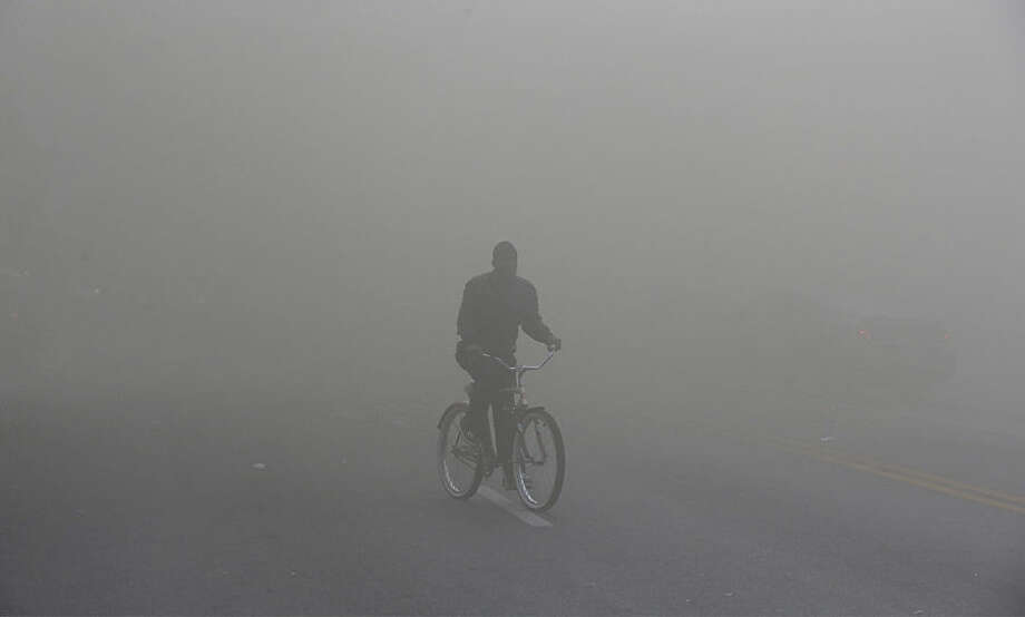 A man rides a bicycle through heavy smoke that is emitting from a nearby store on fire, Monday, April 27, 2015, during unrest following the funeral of Freddie Gray in Baltimore. (AP Photo/Patrick Semansky)