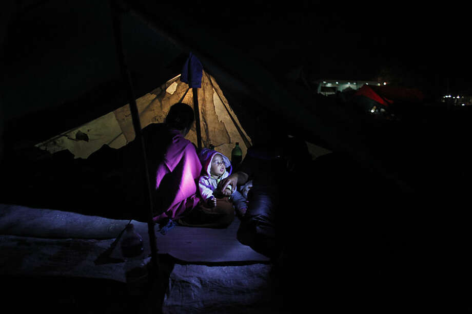 A Nepalese woman sits inside in a tent with her child as people stay on open ground from fears of earthquake tremors in Kathmandu, Nepal, Monday, April 27, 2015. A strong magnitude earthquake shook Nepal's capital and the densely populated Kathmandu valley on Saturday devastating the region and leaving tens of thousands shell-shocked and sleeping in streets. (AP Photo/Niranjan Shrestha)