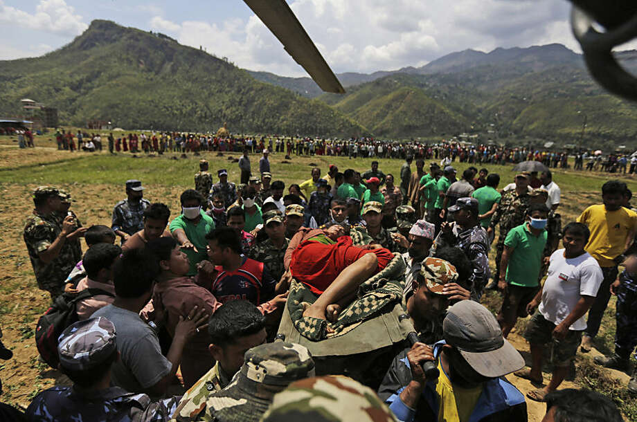 Nepalese soldiers carry a wounded woman to a waiting Indian air force helicopter as they evacuate victims of Saturday's earthquake from Trishuli Bazar to Kathmandu airport in Nepal, Monday, April 27, 2015. The death toll from Nepal's earthquake is expected to rise depended largely on the condition of vulnerable mountain villages that rescue workers were still struggling to reach two days after the disaster. (AP Photo/Altaf Qadri)