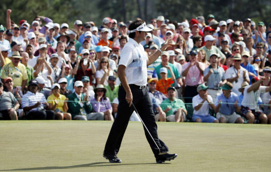 Bubba Watson waves to the gallery after a birdie putt on the ninth hole during the fourth round of the Masters golf tournament Sunday, April 13, 2014, in Augusta, Ga. (AP Photo/Matt Slocum)