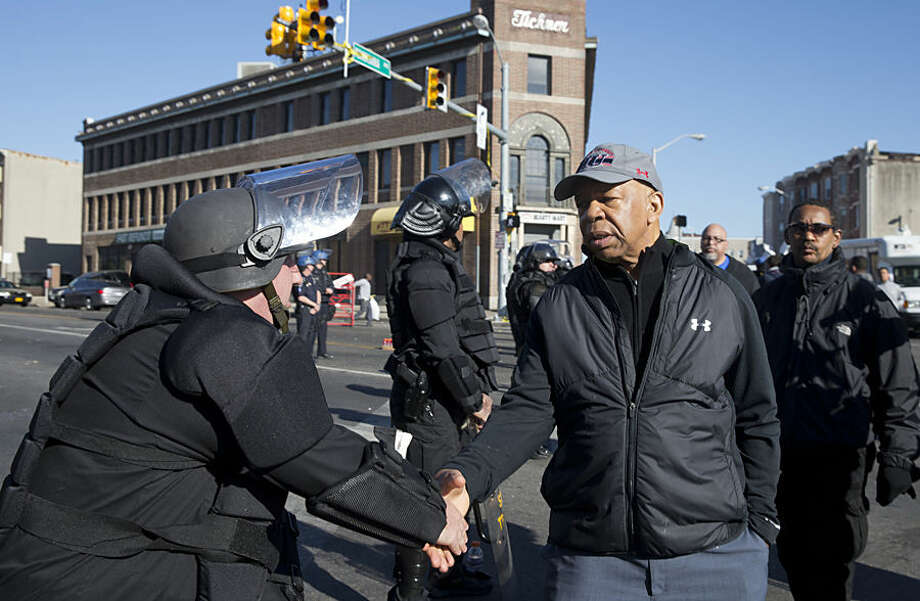 U.S. Rep. Elijah Cummings, D-Md., shakes hands with a Maryland State Trooper Tuesday, April 28, 2015, in the aftermath of rioting following Monday's funeral for Freddie Gray, who died in police custody. The violence that started in West Baltimore on Monday afternoon had spread to East Baltimore and neighborhoods close to downtown and near Camden Yards. (AP Photo/Matt Rourke)