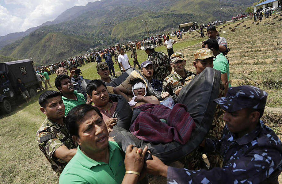 Nepalese soldiers carry a wounded man on a makeshift stretcher to a waiting Indian air force helicopter as they evacuate victims of Saturday's earthquake from Trishuli Bazar to Kathmandu airport in Nepal, Monday, April 27, 2015. The death toll from Nepal's earthquake is expected to rise depended largely on the condition of vulnerable mountain villages that rescue workers were still struggling to reach two days after the disaster. (AP Photo/Altaf Qadri)