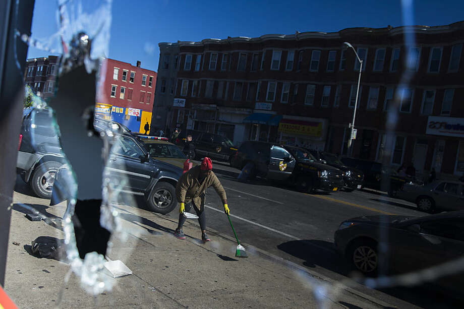 Residents clean up after an evening of riots on Tuesday, April 28, 2015, in Baltimore. National Guard troops fanned out through the city, shield-bearing police officers blocked the streets and firefighters doused still-simmering blazes early Tuesday as a growing area of Baltimore shuddered from riots following the funeral of Freddie Gray who died in police custody. (AP Photo/Evan Vucci)