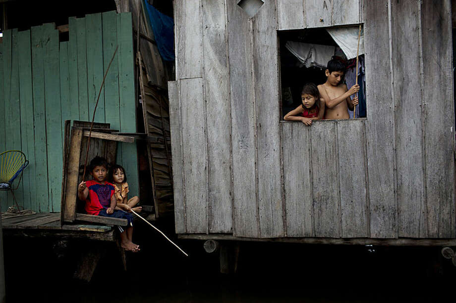 """In this April 19, 2015 photo, children fish from their home sitting just above the water line in the Belen neighborhood of Iquitos, a community in Peru's Amazon nicknamed """"Venice of the Jungle."""" Along with the homes, the community boasts a Roman Catholic and various evangelical churches. It even has bordellos, discoteques, lumber mills and casinos. Many inhabitants work in a market in a nearby area that never floods, selling shad and other fish they catch in the river. (AP Photo/Rodrigo Abd)"""