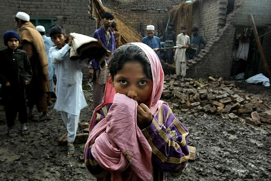 People salvage what they can from a house that collapsed from heavy rain and windstorm that reached up to a speed of 120 kph (75 mph) Sunday evening which collapsed hundreds of buildings, uprooted trees, and electric poles, in Peshawar, Pakistan, Monday, April 27, 2015. Officials say death toll has risen to at least 44. (AP Photo/Mohammad Sajjad)
