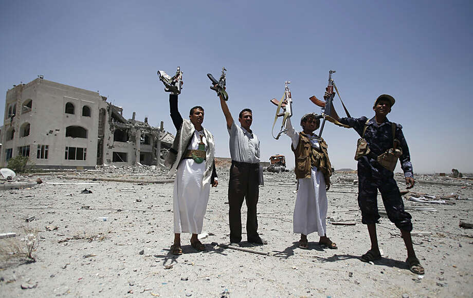 Shiite fighters, known as Houthis, hold up their weapons as they chant slogans at the residence of a military commander of the Houthi militant group, destroyed by a Saudi-led airstrike in Sanaa,, Yemen, Tuesday, April 28, 2015. A security official in Saudi Arabia says a soldier has been killed and another wounded in a gunfight with Shiite Houthi rebels along the kingdom's southern border with Yemen. (AP Photo/Hani Mohammed)