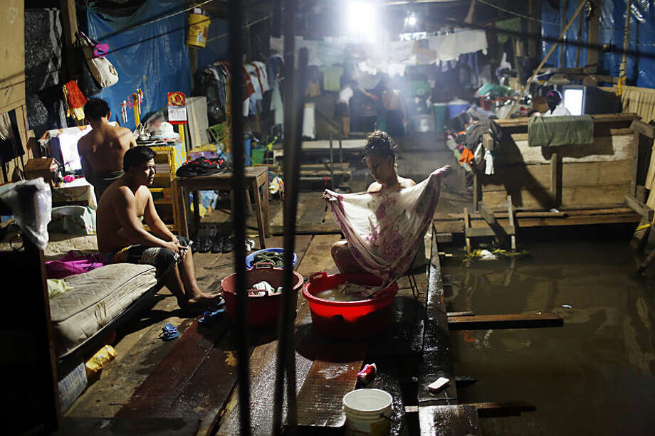 "In this April 20, 2015 photo, Milagros Chumbe washes clothes inside her flooded home in Belen, an Amazon community nicknamed ""Venice of the Jungle,"" in Iquitos, Peru. Sixteen members from three different families live at the home, currently flooded by the rising of the Itaya river. During the rainy season, mothers keep a close eye on toddlers just learning how to walk to ensure they don't fall in the water, and the local press reports on one or two children drowning each year. (AP Photo/Rodrigo Abd)"