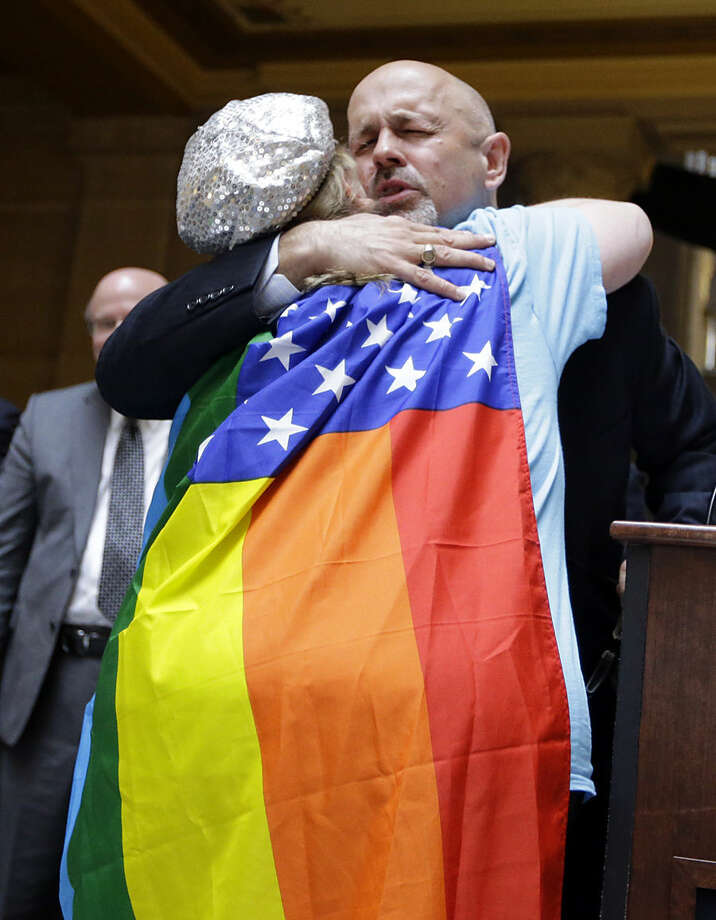 Executive Director of the Indiana Pastors Alliance Ron Johnson, pastor of Living Stones Church in Crown Point, Ind. hugs Kim Saylor of Rainbow Picketing after she interrupted his speech at a rally at the Statehouse in Indianapolis, Monday, April 27, 2015 against the revised religious freedom legislation. The group of conservative religious leaders is rebuking Gov. Mike Pence and the leaders of the Republican-dominated General Assembly for changes to Indiana's religious objections law that they claim threaten religious liberties.(AP Photo/Michael Conroy)